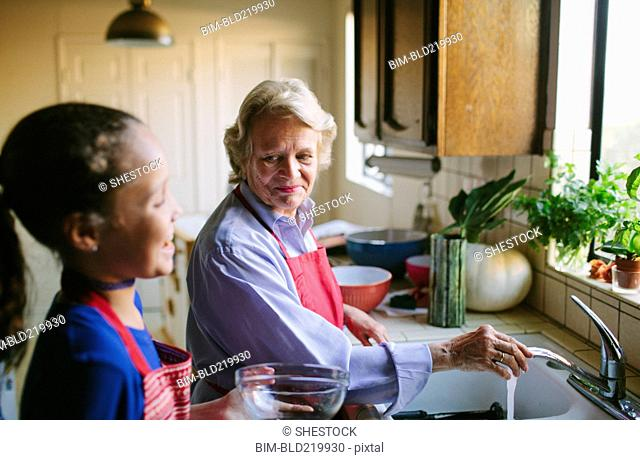 Grandmother and granddaughter washing bowl in kitchen sink