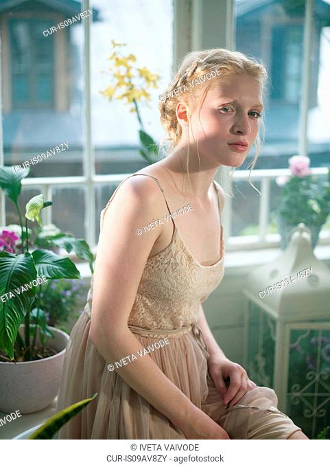 Young woman, with blonde plaited hair, in room filled with plants, looking away