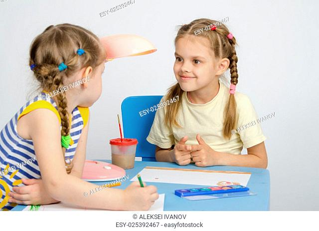 Two girls of four and six years of sitting at the table and draws and paints and pencils
