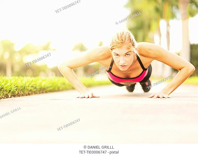 Woman doing pushups outdoors