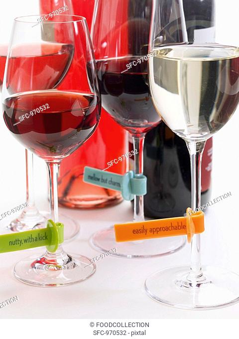 Glasses of wine with plastic labels describing the wine, bottles