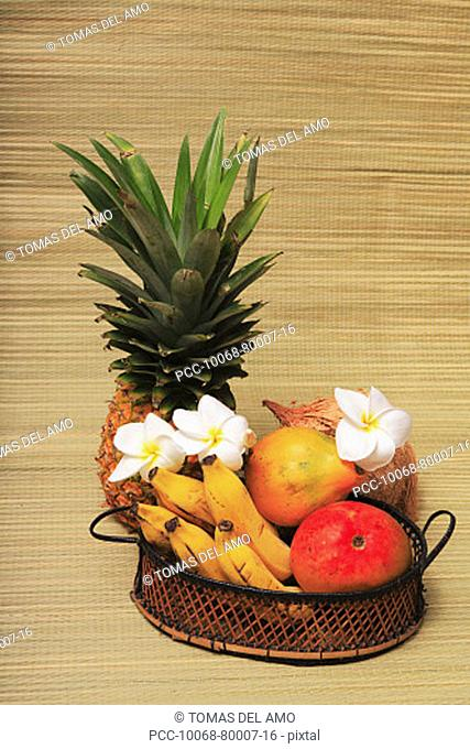 Variety of exotic tropical fruits in a basket with plumerias on a woven mat background