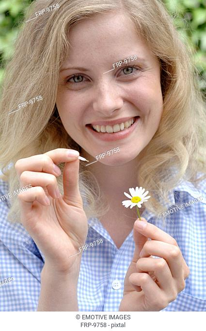 Happy woman plucking petals from daisy
