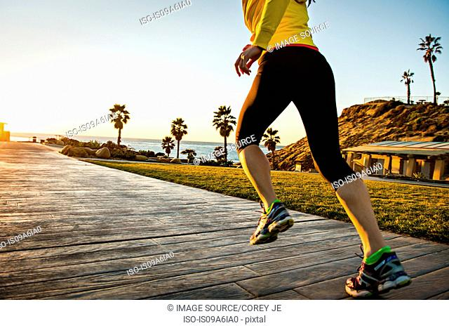 Woman running on wooden path
