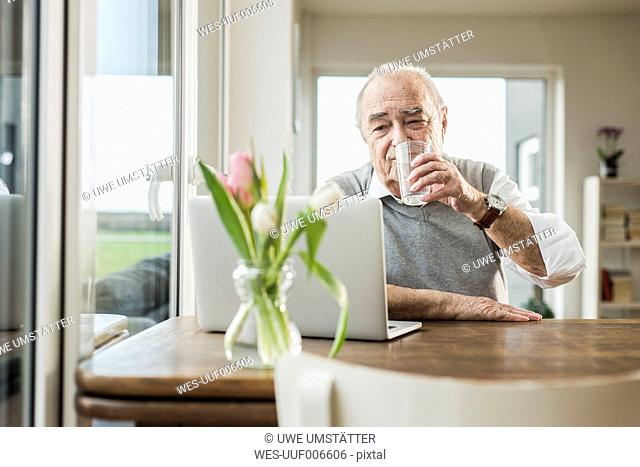 Portrait of senior man with laptop drinking glass of water at home