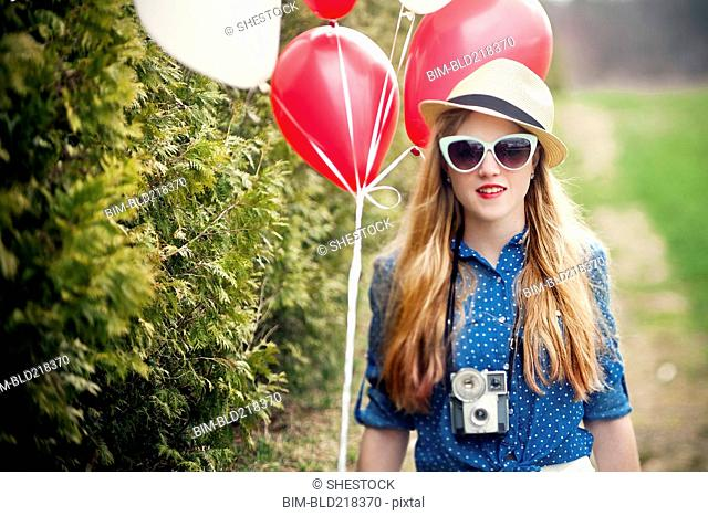 Caucasian woman carrying balloons and instant camera