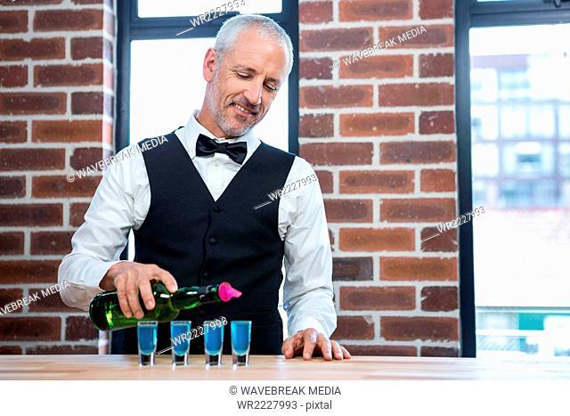 Barman pouring blue shots