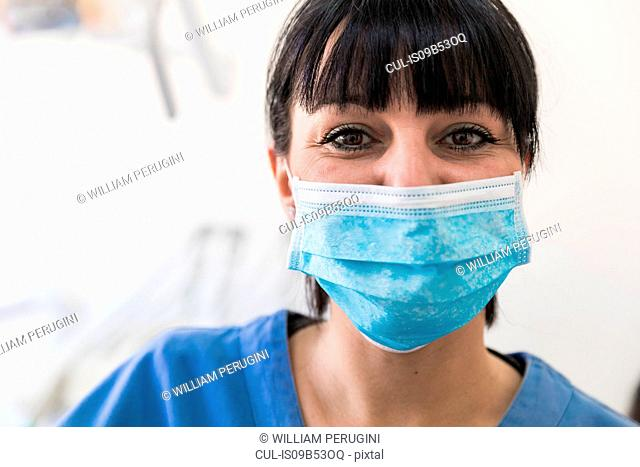 Portrait of female dentist in blue surgical mask