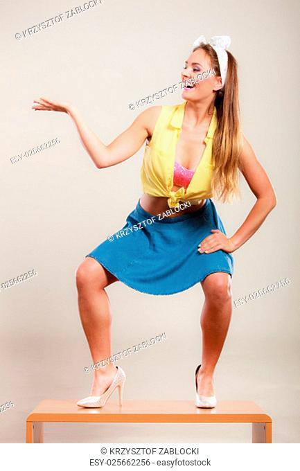 alluring seductive pretty pin up girl wearing a hairband bow,skirt and high heels. attractive retro gorgeous young woman dancing on table with empty hand palm...
