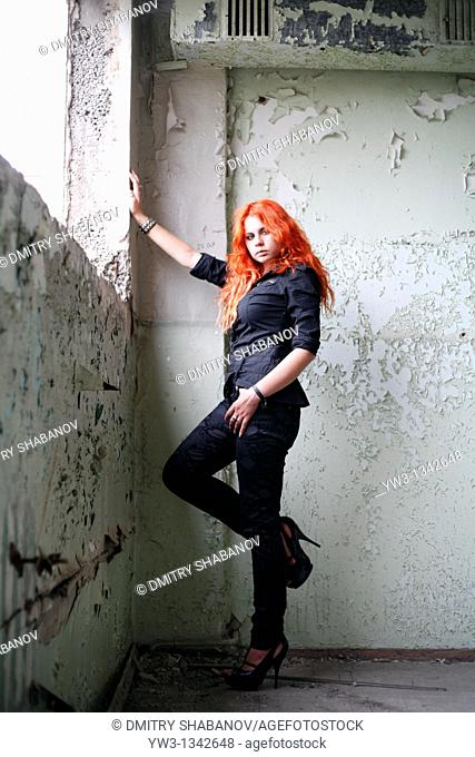 pretty redhead girl indoors in obsolete room
