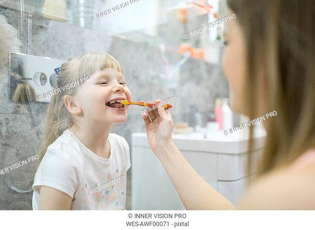 Mother brushing teeth of her daughter in bathroom