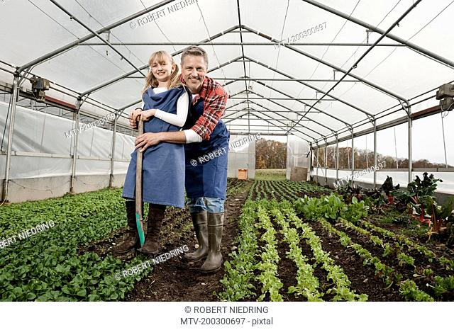 Father and daughter in greenhouse