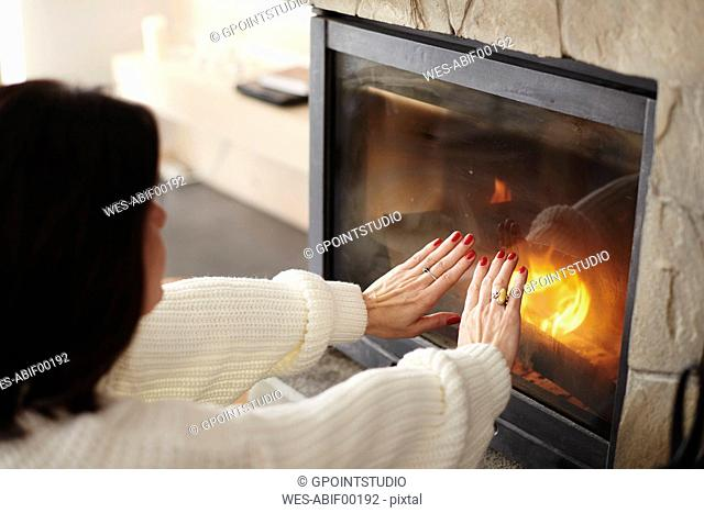 Mature woman warming her hands at the fireplace