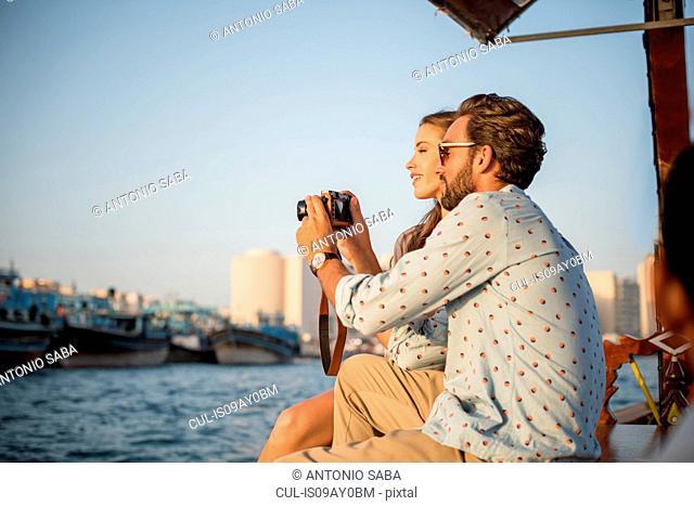 Romantic couple reviewing camera on boat at Dubai marina, United Arab Emirates