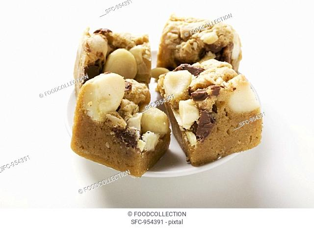 Small pieces of chocolate slice with macadamia nuts on plate