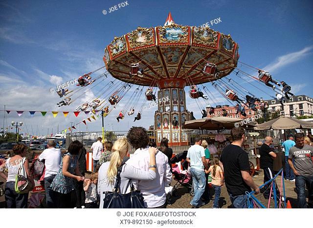 couple standing watching chair-o-plane fairground funfair ride bangor county down northern ireland uk