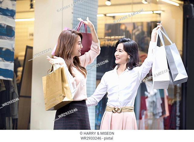 Smiling mother and daughter shopping