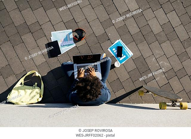 Young businessman sitting outdoors at a wall working on laptop