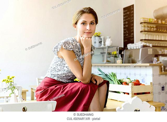 Young woman sitting on cafe table looking at camera, portrait