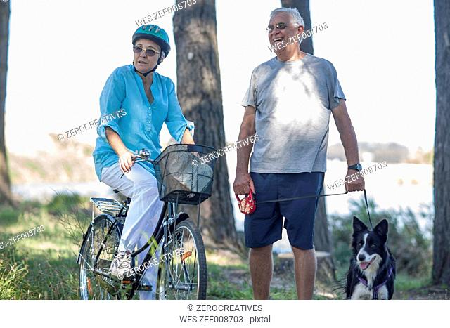 Elderly couple with dog and bicycle in forest