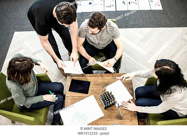 Four people seated at a table using coloured pens on paper, colleagues at a planning meeting