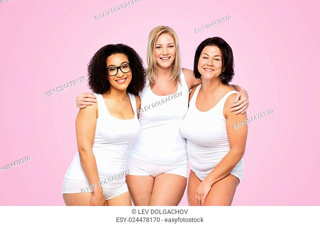 friendship, beauty, body positive and people concept - group of happy plus size women in white underwear over pink background