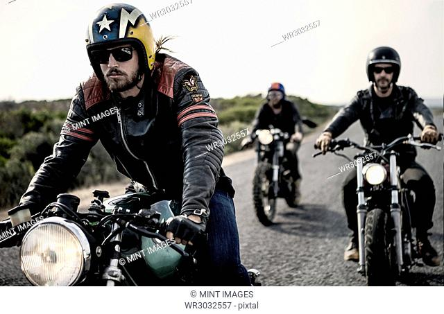 Three men wearing open face crash helmets and sunglasses riding cafe racer motorcycles along rural road