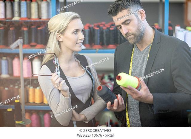 Fashion designer and seamstress examining cotton reels