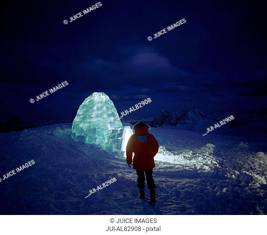 Hiker walking to illuminated igloo at night