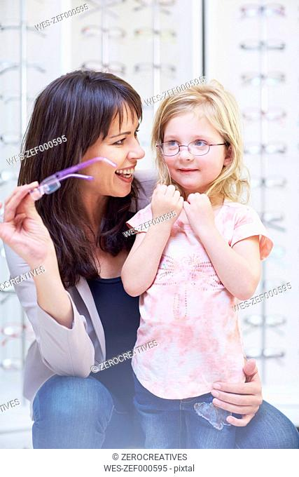 Girl at the optician trying on glasses
