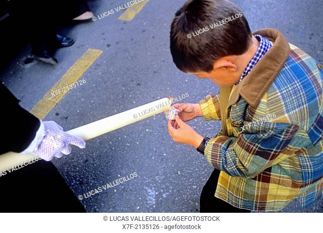 Penitent and boy.Boy making a ball of wax.Brotherhood of `Resucitado de Regina'.Resurrection Sunday procession. Granada. Andalusia, Spain