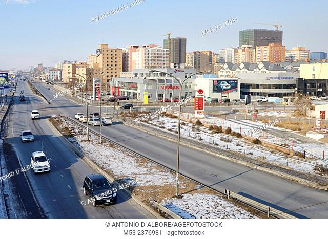 Vehicles along Narnii Road, a busy commercial area in Sukhbaatar District. In the background a newly built residential estate. Ulaanbaatar. Mongolia