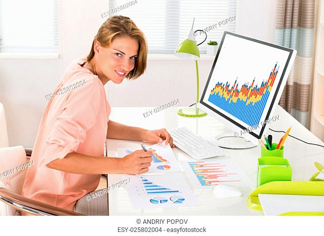 Young Happy Woman Analyzing Financial Statistics In Office