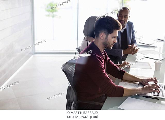 Businessman working at laptop in conference room meeting