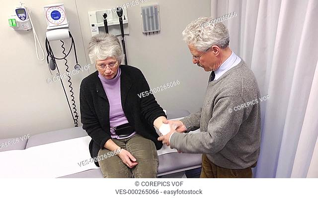 Doctor applying a bandage to an injured woman's hand inside a doctor's practice with various medical equipment