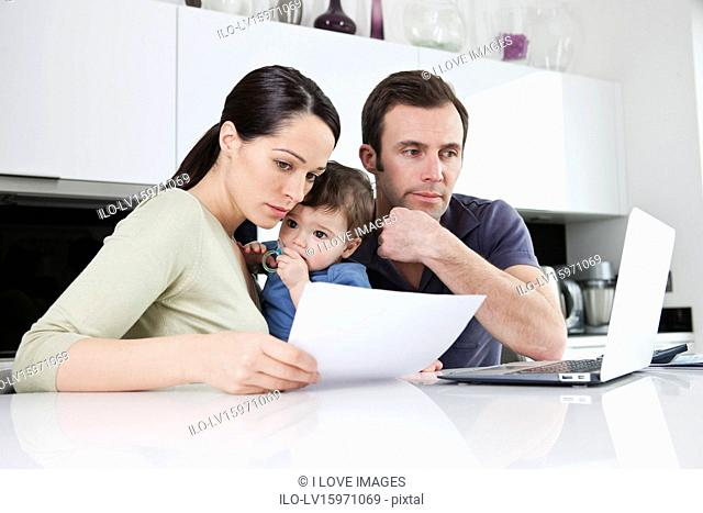 A couple and their baby son looking at their household finances