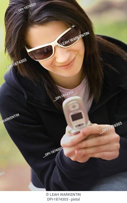 edmonton, alberta, canada, a woman uses her cell phone