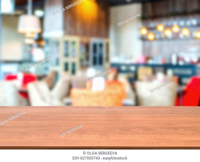 Dark wooden board empty table in front of blurred background. Perspective brown wood over blur in cafe interior - can be used for display or montage our...