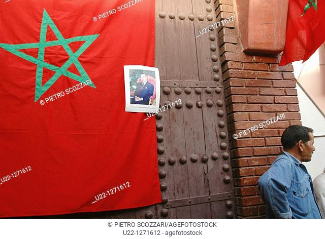 Marrakesh (Morocco): the Moroccan flag, with the king's photo, by Djemaa el Fna Square