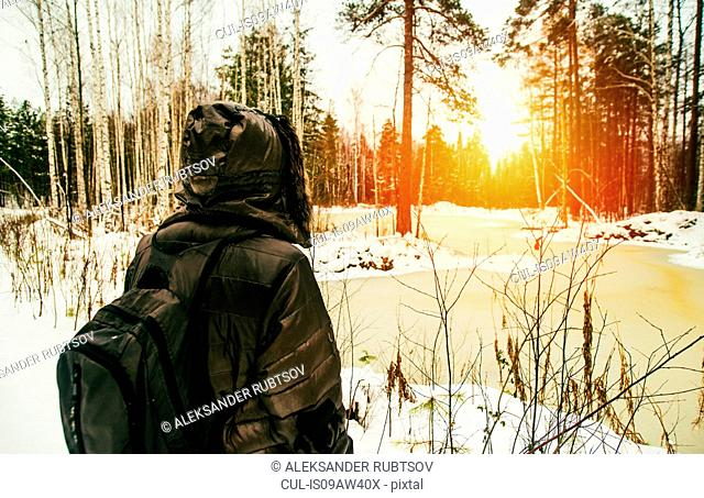 Man hiking through snowy landscape at sunset, rear view, Russia