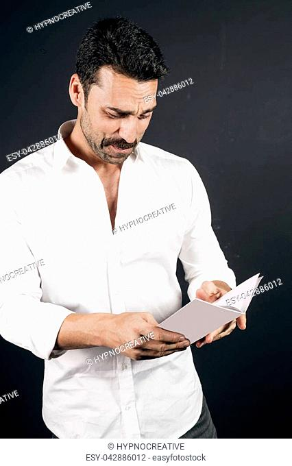Young handsome man with beard and moustache reading a brochure against black background, studio portrait