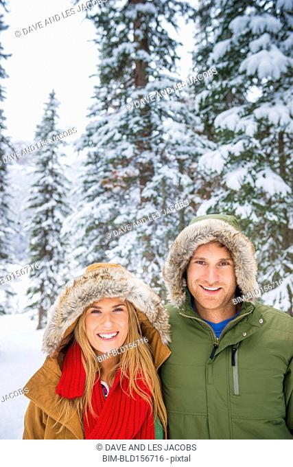 Caucasian couple smiling in snowy forest
