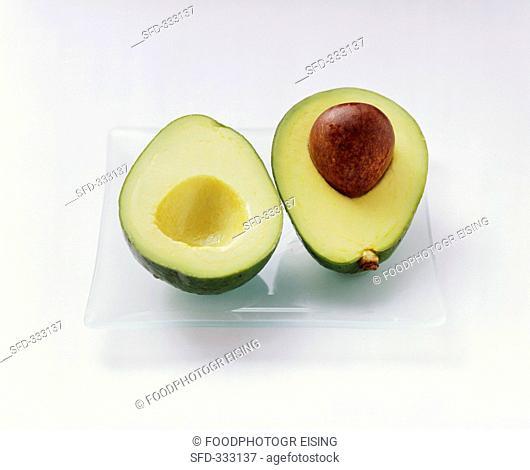 A halved avocado on a glass plate