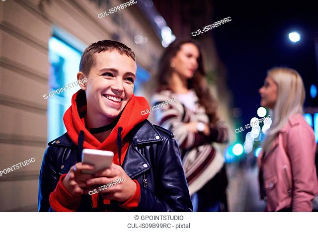 Young woman with smartphone laughing on city street at night