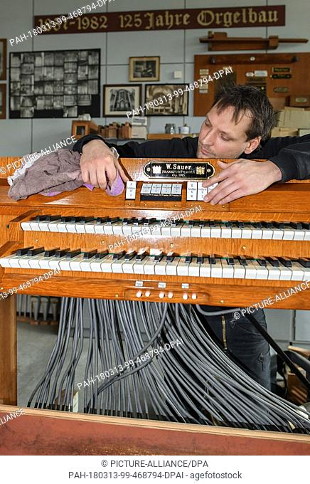 13 March 2018, Muellrose, Germany: The organ builder Tobias Mutke from the company W. Sauer Organ Build Frankurt (Oder) Ltd working on console of an organ built...