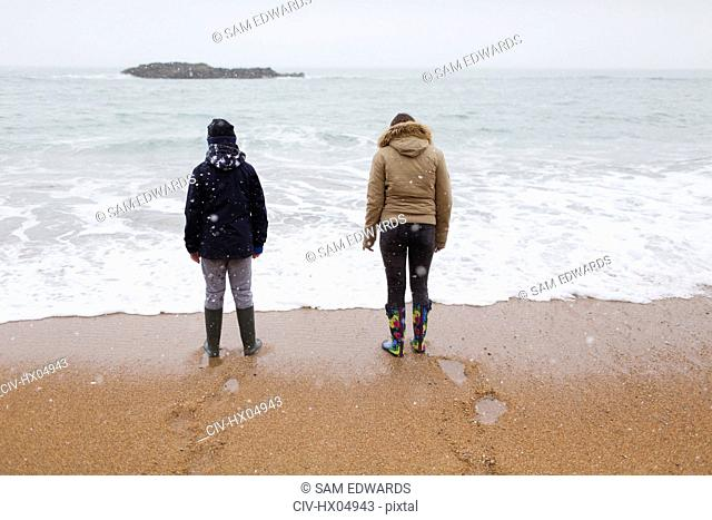 Brother and sister in warm clothing standing on snowy winter beach