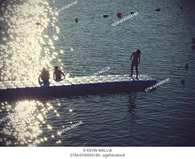 Young Boys on a floating jetty at Sundown