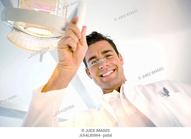 Male dentist smiling and adjusting dental light