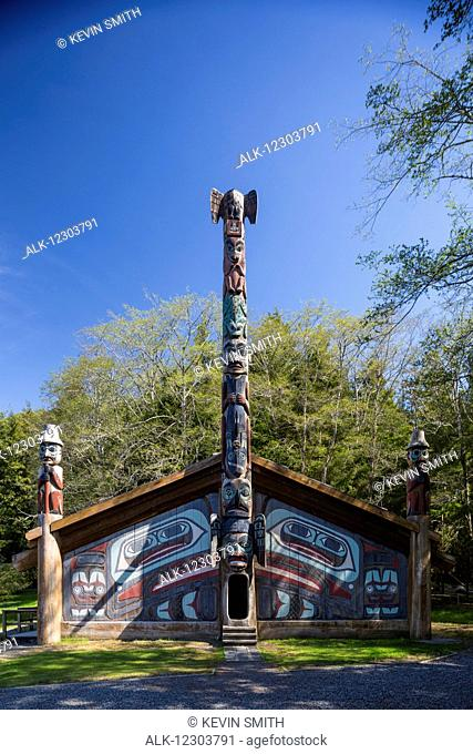 Totem poles outside a large clan house painted with images of the raven, Totem Bight Historic State Park, Ketchikan, Southeast Alaska, USA, Spring