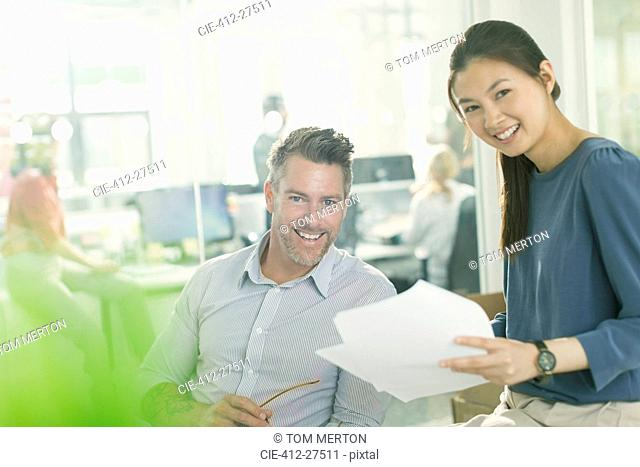 Portrait smiling business people reviewing paperwork in office